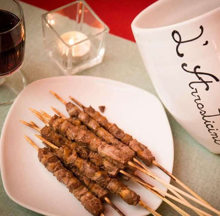 Arrosticini  serviti a tavola accompagnati da vino rosso dell'osteria l'arrosticini