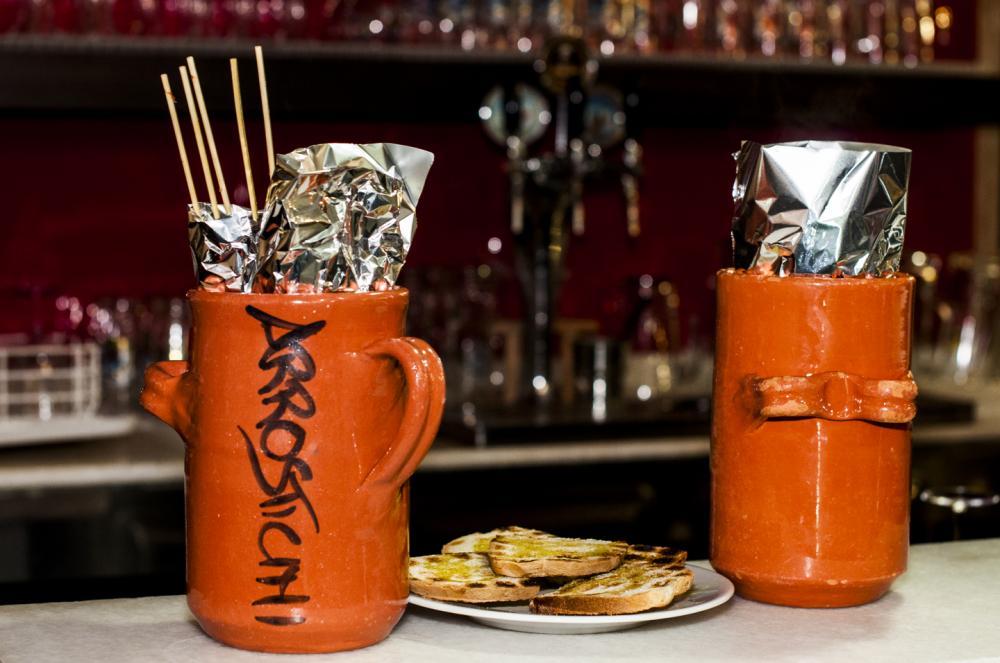 Vasi in ceramica contenenti i tradizionali Arrosticini abruzzesi, serviti con bruschette