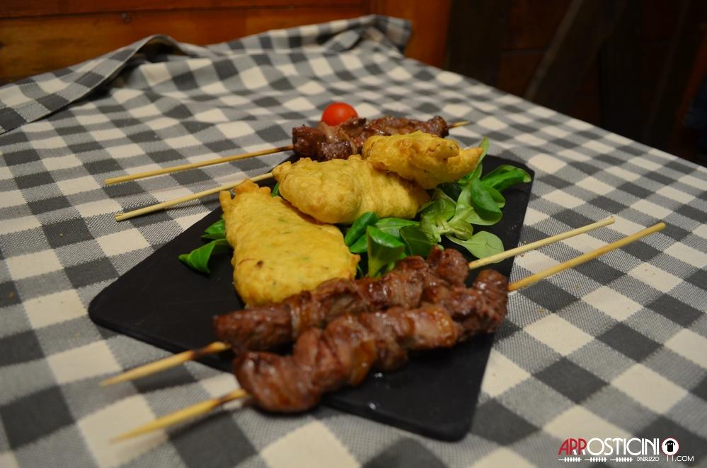 arrosticini e valeriana con pane e olio in piatto nero km431 ristorante Silvi Abruzzo