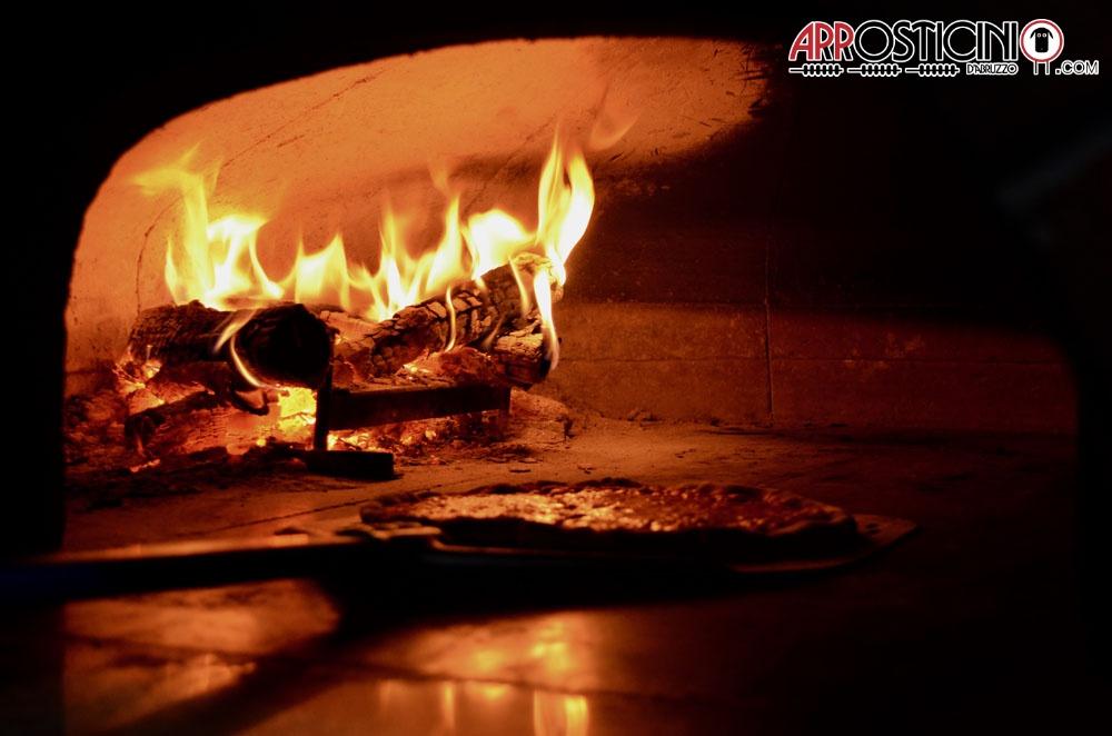 Pizza sulla pala nel forno a legna