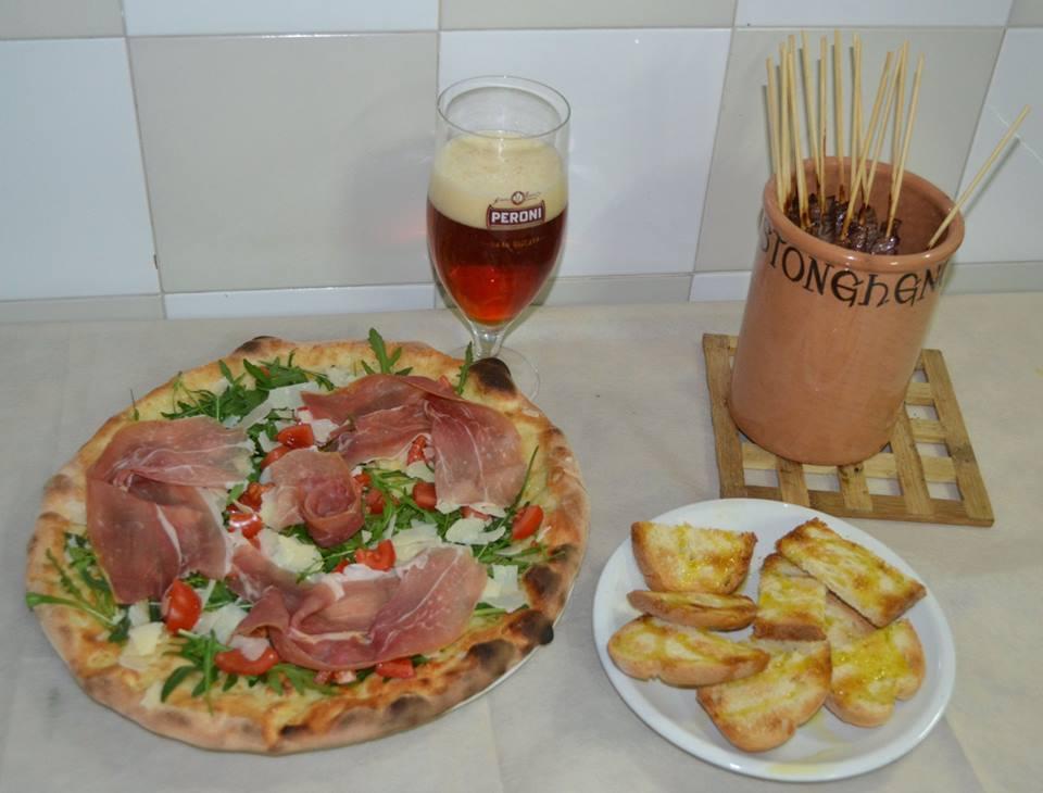 Arrosticini abruzzesi, birra rossa, pizza e bruschette con olio.